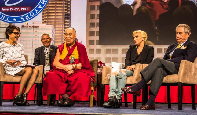 Ann Curry (L) moderates a question and answer session with the Dalai Lama, Lady Gaga, and philanthropist Philip Anschutz during the 84th Annual Meeting of the United States Conference of Mayors on June 26, 2016 in Indianapolis, Ind. Seated behind is translator Thupten Jinpa. Photo by Edwin Locke/UPI