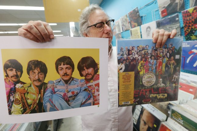 Customer service represenative Joe Steinman reads the back of the Beatles' Sgt. Peppers album and a poster being given away at Vintage Vinyl Records in University City, Mo., on the 50th anniversary of the release of the album in the United States, on June 2. On August 14, 1985, Michael Jackson paid $47 million at auction for the rights to 40,000 songs, including most of the Beatles classics. Photo by Bill Greenblatt/UPI