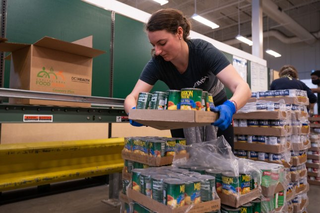 A volunteer packs a box of food to be distributed to people in need at the Capital Area Food Bank on April 9, 2020, in Washington, D.C. New research suggests older adults are more willing than their younger peers to exert effort on someone else's behalf. Photo by Kevin Dietsch/UPI
