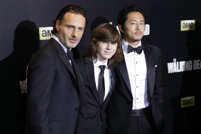 Left to right, Andrew Lincoln, Chandler Riggs, and Steven Yeun arrive at AMC's The Walking Dead Season 6 premiere on October 9, 2015 in New York City. The network said it is planning a series of TV movies set in TWD universe. File Photo by John Angelillo/UPI
