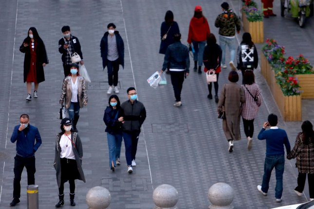 People wear protective face masks to guard against spread of the coronavirus disease on Tuesday while visiting a shopping area in Beijing, China. Photo by Stephen Shaver/UPI