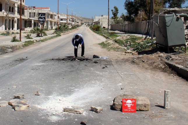 A Syrian man collects samples from the site of a suspected toxic gas attack in Khan Sheikhun, in Syria's northwestern Idlib province, on April 5, 2017. The Organization for the Prohibition of Chemical Weapons on Wednesday accused the Syrian regime of using chemical weapons in three other attacks earlier that year. File Photo by Omar Haj Kadour/UPI