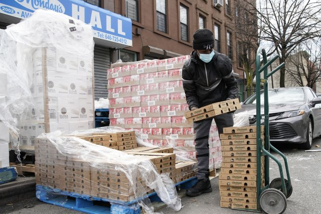 A worker puts cartons of food on a hand truck as New York City Mayor Bill de Blasio visits The Campaign Against Hunger food pantry in New York City on Tuesday.. Photo by John Angelillo/UPI