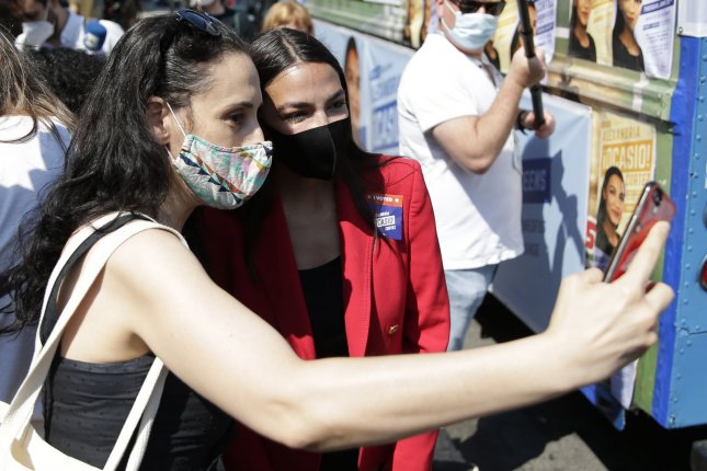 Rep. Alexandria Ocasio-Cortez of New York, who is up for re-election in November, poses for a photo with a young supporter on the day of the New York primary election, June 23, in New York City. Photo by John Angelillo/UPI