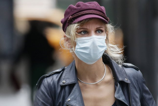 A masked woman walks in Times Square in New York City on Wednesday. Neighborhoods in the boroughs of Brooklyn and Queens have seen a slight uptick in coronavirus cases, officials say. Photo by John Angelillo/UPI