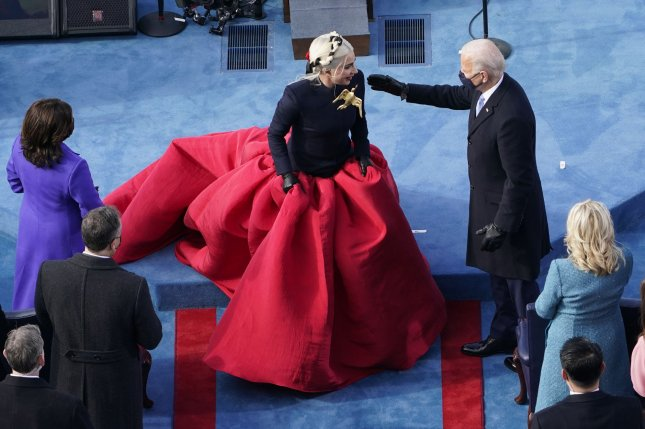 Lady Gaga (L) sported a red and navy Schiaparelli dress with a large gold dove brooch to sing the national anthem at President Joe Biden's inauguration Wednesday in Washington, D.C. Pool Photo by Susan Walsh/UPI