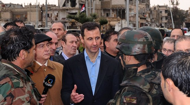 Syria's President Bashar al-Assad (C) speaks to soldiers during a tour in the Baba Amr neighborhood of Homs in this handout photograph released by Syria's national news agency SANA on March 27, 2012. UPI