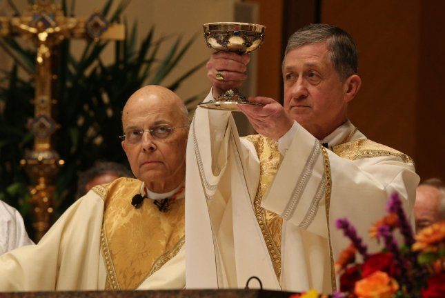 Cardinal Francis George (L) watches as Archbishop Blase Cupich raises the communion chalice during his Installation Mass at Holy Name Cathedral in Chicago on November 18, 2014 in Chicago. Cupich is succeeding George as Archbishop of Chicago. UPI/Antonio Perez/Pool