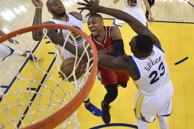Portland Trail Blazers guard Damian Lillard (C) goes to the basket as Golden State Warriors center Marreese Speights (L) and Golden State Warriors forward Draymond Green (R) defend during their NBA Western Conference semifinal game five at Oracle Arena in Oakland, California, on May 11, 2016. Pool photo by John G. Mabanglo/UPI