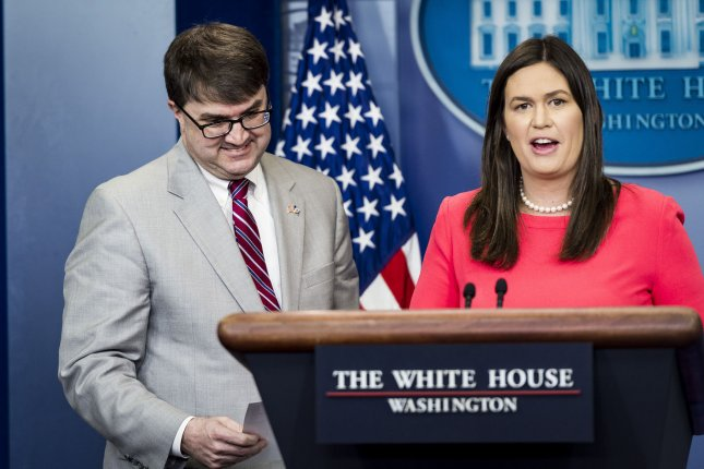 Acting Veterans' Affairs secretary Robert Wilkie (L) accepts President Trump's donation of his 2018 first quarter salary from White House Press Secretary Sarah Sanders during a press briefing at the White House on Thursday in Washington, D.C. Wilkie accepted the donation which was given to support the Veterans' Affairs caregiver programs. Photo by Pete Marovich/UPI