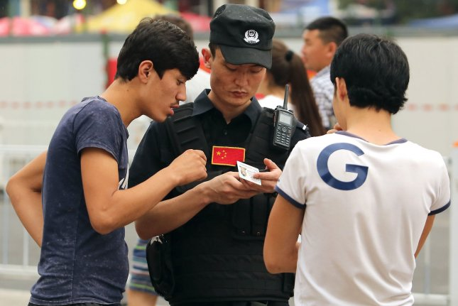 Chinese military police check the identification of Uyghur and Kazak men next to a mosque and tourist center during Ramadan in the Xinjiang province on June 27, 2015. A senior Chinese official announced Tuesday that most of the Uyghur and other Muslim minorities held in internment camps have been released. File Photo by Stephen Shaver/UPI