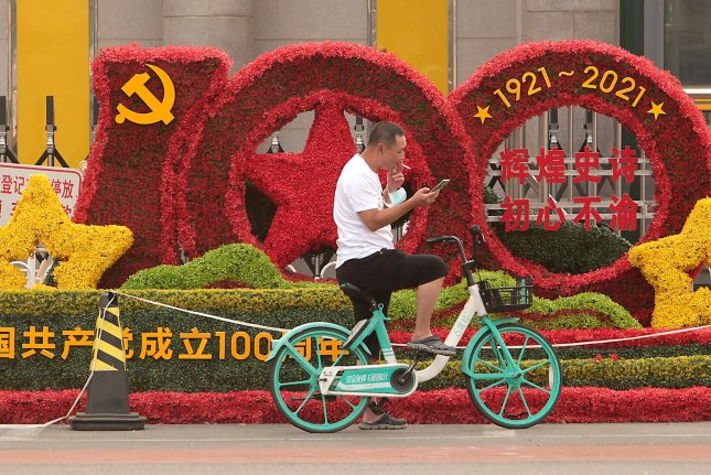 A man uses his phone by a display in front of a military base celebrating the 100th anniversary of the Communist Party in Beijing, on August 8, 2021. File Photo by Stephen Shaver/UPI