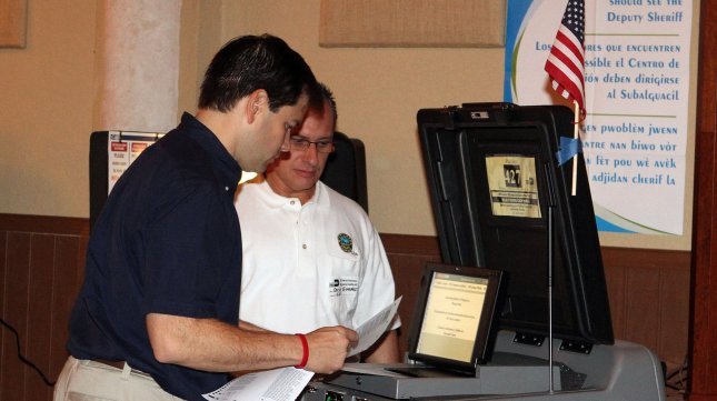 Florida Senator Marco Rubio (L) casts his vote on Election Day in 2010. The U.S. Justice Department said Florida was in violation of a provision of the National Voter Registration Act that forbids purging voters within 90 days of an election.UPI/Martin Fried