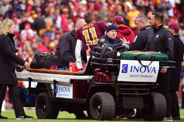 Washington Redskins quarterback Alex Smith (11) is helped off the field after being injured in the third quarter against the Houston Texans on Sunday at FedEx Field in Landover, Md. Photo by Kevin Dietsch/UPI