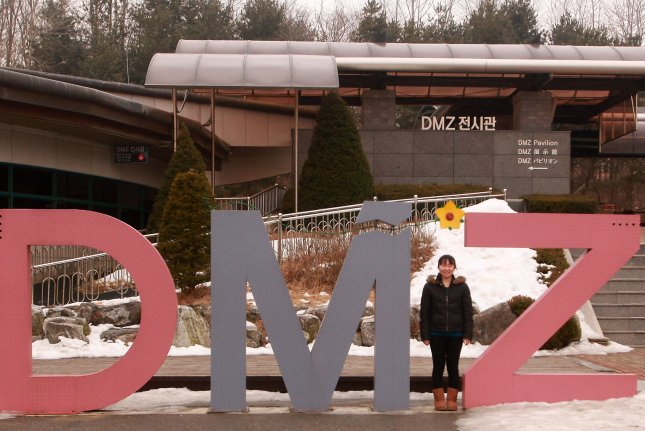 A tourist poses for a photo at a visitor center in part of the Demilitarized Zone near Seoul in 2013. File Photo by Stephen Shaver/UPI