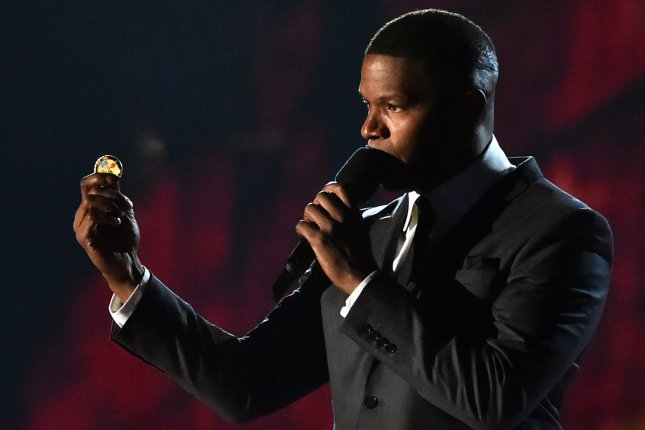 Jamie Foxx holds a challenge coin on stage during the Concert for Valor on the National Mall on Veteran's Day, Nov. 11, 2014, in Washington, D.C. Photo by Kevin Dietsch/UPI