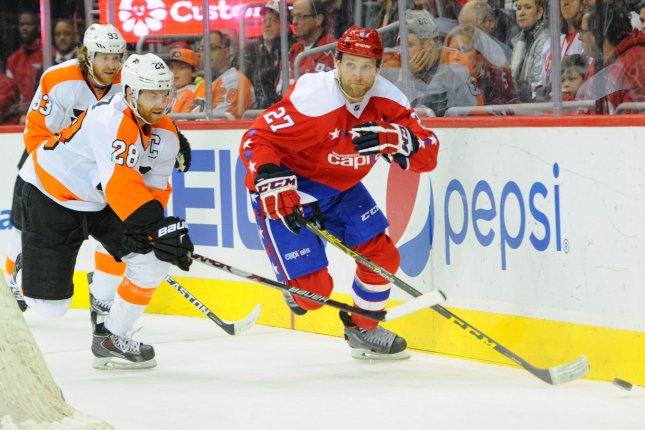 Washington Capitals defenseman Karl Alzner (27) works the puck against Philadelphia Flyers center Claude Giroux (28) in the first period at the Verizon Center in Washington, D.C. on February 7, 2016. Photo by Mark Goldman/UPI