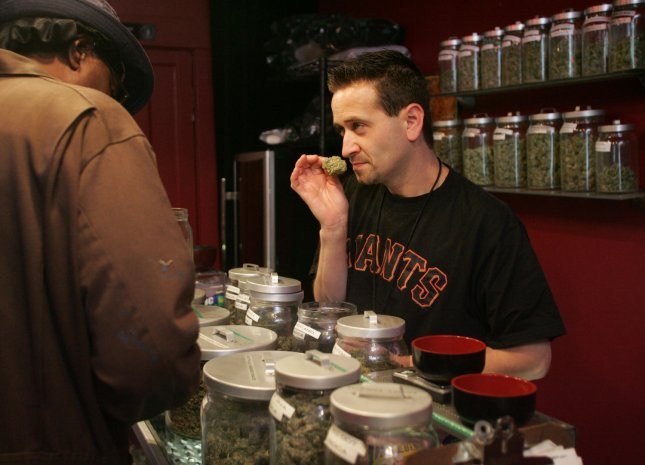 Sativa Steve (R) smells a marijuana bud as he waits on a customer in a medicinal cannabis shop in San Francisco on June 7, 2005. (UPI Photo/Terry Schmitt)