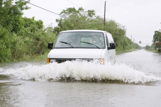 A van tries to naviagte through flood waters in the Redlands section of Miami, Florida. (File/UPI/Michael Bush)
