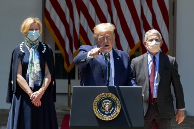 President Donald J. Trump (C) delivers remarks Friday regarding coronavirus vaccine developments in the Rose Garden of the White House in Washington D.C. Dr. Deborah L. Birx (L), White House Coronavirus Response Coordinator and Dr. Anthony Fauci, Director of the National Institute of Allergy and Infectious Diseases at the National Institutes of Health, listen behind the president. Photo by Stefani Reynolds/UPI