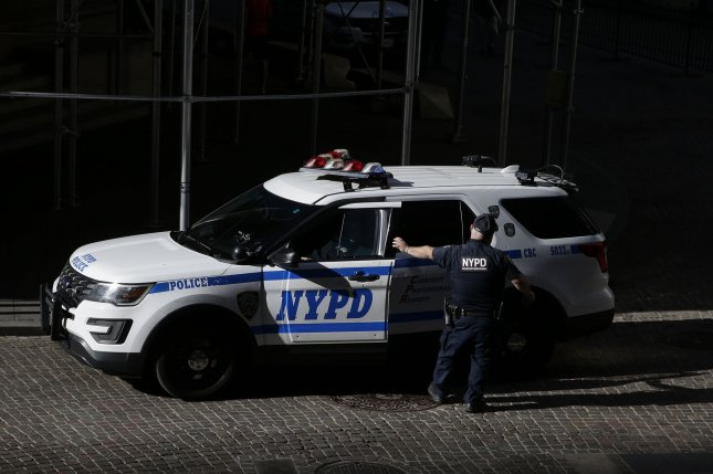 An NYPD Police Officer exits a police car on Wall Street in New York City in this October file photo. Photo by John Angelillo/UPI