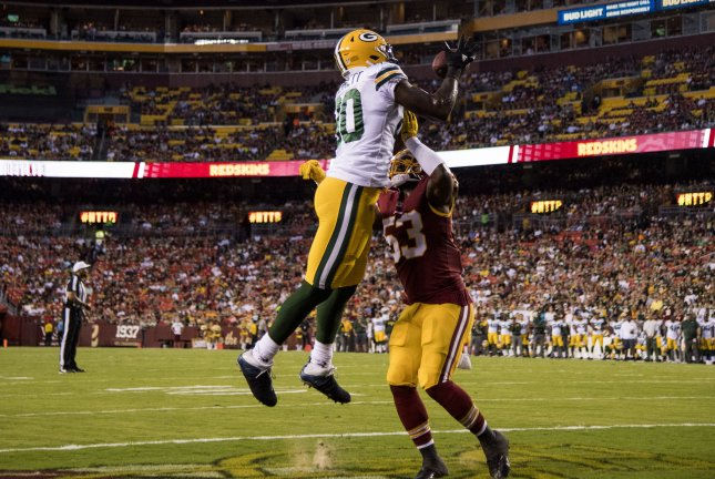 Former Green Bay Packers tight end Martellus Bennett hauls in a touchdown pass against Washington Redskins linebacker Zach Brown during a preseason game in August. Photo by Kevin Dietsch/UPI