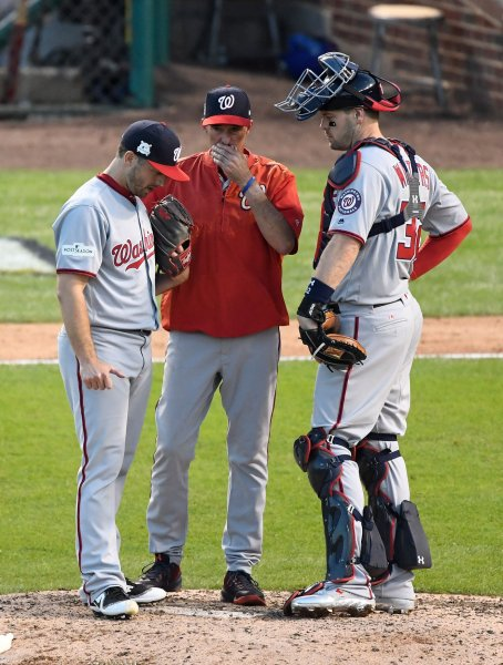 Brandon Kintzler, left, talks Washington Nationals pitching coach Mike Maddux, center, with catcher Matt Wieters during a game against the Chicago Cubs. Photo by Brian Kersey/UPI