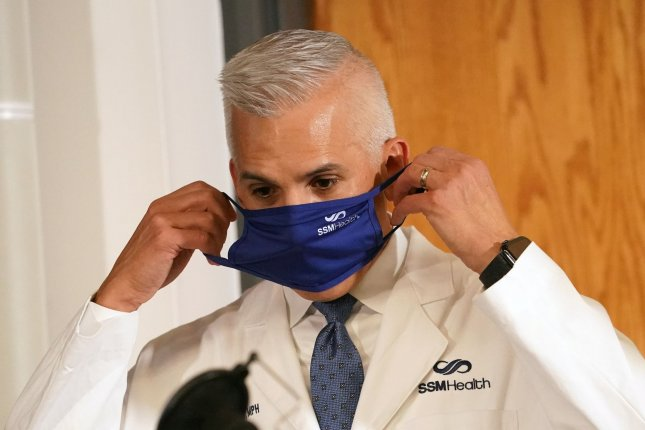 St. Louis Metropolitan Pandemic Task Force leader Dr. Alexander Garza puts on his face mask after speaking about the effect coronavirus has had on the front-line workers during his daily report Friday at Saint Louis University. Photo by Bill Greenblatt/UPI