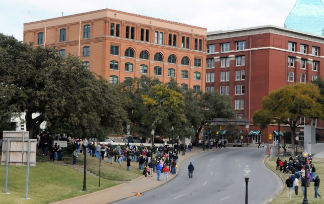 Visitors gather in Dealey Plaza on November 22, 2008 to commemorate the 45th anniversary of the assassination of U. S. President John F. Kennedy Dallas, TX. The building on the left is the Texas School Book Depository, the building where Lee Harvey Oswald fired his shots from. Kennedy was shot on November 22, 1963 as he rode down Elm Street in Dallas. The anniversary of his death brings history buffs, JFK fans and conspiracy theoryists back to the site. (UPI Photo/Ian Halperin)