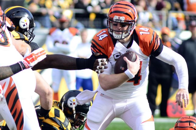 Cincinnati Bengals quarterback Andy Dalton (14) evades the reach of Pittsburgh Steelers defensive end Cam Thomas (93) and gains five yards in the first quarter at Heinz Field in Pittsburgh on November 1, 2015. Photo by Archie Carpenter/UPI