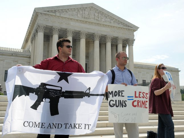 Pro-gun rights protesters hold signs in front of the Supreme Court in Washington as they wait for the Court's decision on the DC handgun ban on June 26, 2008. The Supreme Court, in a 5-4 ruling, struck down Washington's handgun ban, affirming the rights of individuals to own firearms. However, the decision should leave most gun laws and regulations intact. (UPI Photo/Roger L. Wollenberg)