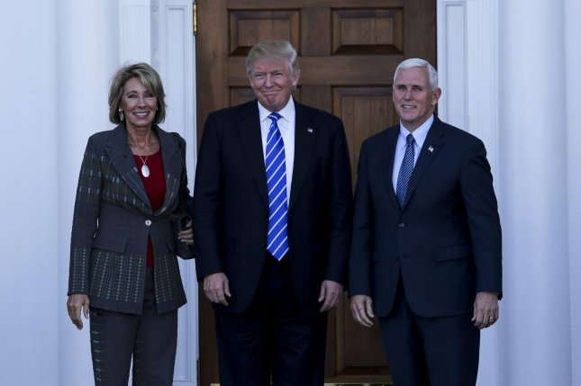 President-elect Donald Trump and Vice President-elect Mike Pence pose with Education Secretary-designate Betsy DeVos after a meeting in November. DeVos is one of several Trump Cabinet designees whose confirmation Democrats are seeking to delay after government ethics officials said they have not commpleted reviews for potential conflicts of interest. File Pool photo by Aude Guerrucc/UPI