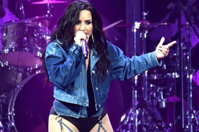 Demi Lovato straddles Kehlani on bed during concert