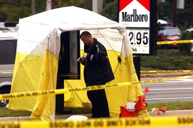A police officer collects evidence at a gas station where a suspect was picked up earlier in connection with the sniper attacks in the Washington area, in Henrico County, Va., October 21, 2002. On December 18, 2003, teenager Lee Malvo was convicted of murder in Washington-area sniper attacks that killed 10 people. He was sentenced to life in prison.File Photo by Chris Cordedr/UPI
