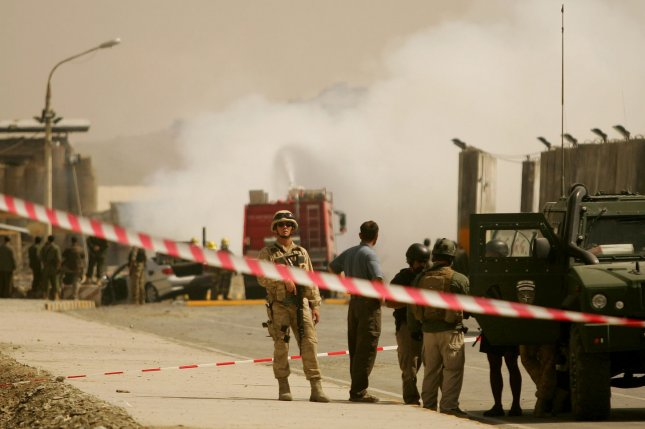 Rescue workers put out the blaze as NATO soldiers stand guard at the scene of a suicide attack in Kabul, Afghanistan on September 8, 2009. A car bomb exploded near the entrance to Kabul's military airport in an apparent attack on an international convoy, killing at least two civilians and wounding six, Afghan officials said. The Taliban claimed responsibility for the blast. File photo. (UPI/Mohammad Kheirkhah)