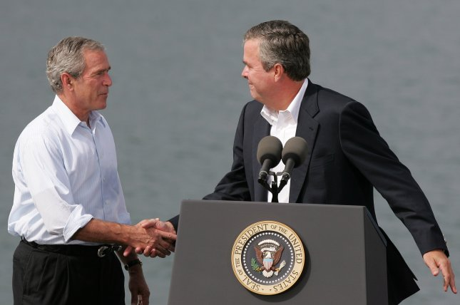 Former Florida Governor Jeb Bush (R) shakes hands with his brother, former U.S. President George W. Bush, who said Thursday he hopes Jeb runs for the White House. (UPI Photo/Ralph Notaro)