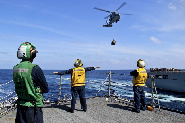 Three sailors on the destroyer USS Kidd help direct helicopter operations during the search for Malaysia Airlines Flight 370, which disappeared over the Indian Ocean March 8, 2014, with 239 people aboard. U..S Navy/UPI/File