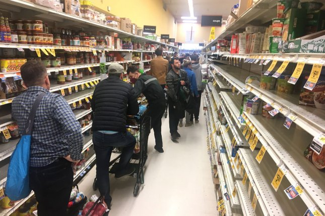 Shoppers wait in long lines as they stock up on supplies during the coronavirus pandemic at a grocery store in San Francisco. File Photo by Terry Schmitt/UPI
