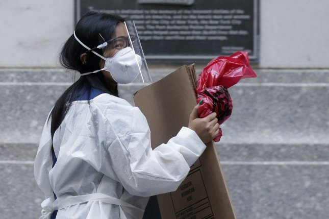 A woman wears a mask, a face shield and other personal protective equipment on Thursday at the New York Stock Exchange on Wall Street in New York City.  Photo by John Angelillo/UPI