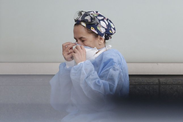A medical worker adjusts her face mask before entering Maimonides Medical Center in New York City on Friday. The number of Americans hospitalized with COVID-19 in the United States has set a new record. Photo by John Angelillo/UPI