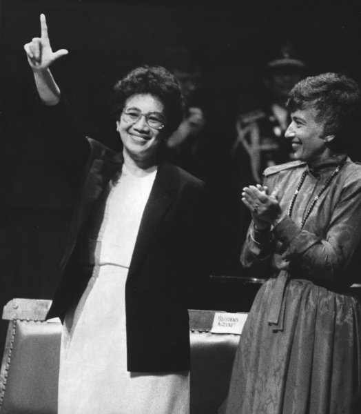 Philippine President Corazon Aquino gives the Philippine revolution sign to a standing ovation at Memorial Hall at Harvard University after delivering her address on September 20, 1986. Matina Horner, President of Radcliffe College (R) looks on. (UPI Photo/George Riley/Files)