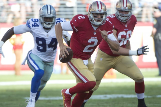 Former San Francisco 49ers quarterback Blaine Gabbert (2) scrambles away from Dallas Cowboys defensive end Randy Gregory (94) in the second quarter on August 23, 2015 at Levi's Stadium in Santa Clara, California. File photo by Terry Schmitt/UPI