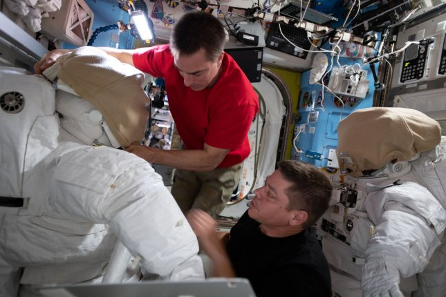 NASA astronauts Chris Cassidy (L) and Robert Behnken prepare their spacesuits in June for a series of spacewalks at the International Space Station, including an assignment planned for Thursday. File Photo courtesy of NASA