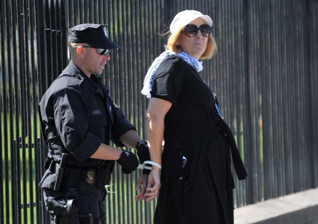 Antiwar activist Cindy Sheehan is arrested as she participates in a demonstration against torture, detentions in Guantanamo Bay and the war in Afghanistan and Iraq, in front of the White House in Washington on October 5, 2009. UPI/Kevin Dietsch.