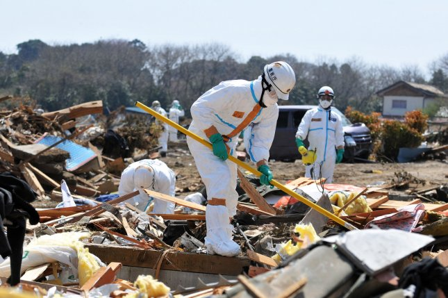 Japanese police wearing chemical protection suits search for victims near the Fukushima Dai-ichi nuclear power plant in Minamisoma, Fukushima prefecture, Japan, on April 15, 2011. A team of Japanese researchers led by Toshihide Tsuda, a professor of environmental epidemiology at Okayama University, said cases of thyroid cancer in Fukushima Prefecture have skyrocketed since March 2011. File Photo by Keizo Mori/UPI