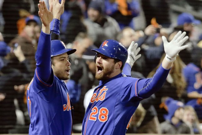 New York Mets batter Daniel Murphy (28) celebrates with on-deck batter Travis d'Arnaud at the dugout steps after he hit a solo home run against the Chicago Cubs in the first inning inning of game 1 of the NLCS at Citi Field in New York City on October 17, 2015. Photo by Ray Stubblebine/UPI