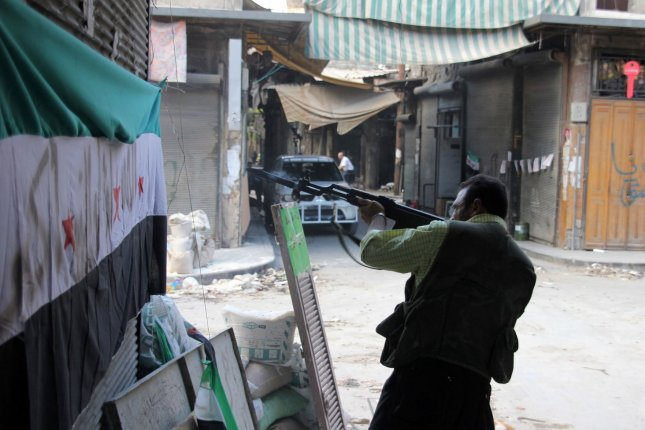 A fighter with the Free Syria Army fires his weapon during skirmishes with government forces in a contested neighborhood in the northern city of Aleppo, Syria, on Sept.12, 2012. UPI/Ahmad Deeb