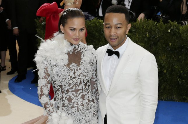 John Legend (R) and Chrissy Teigen helped daughter Luna toss a ball to Robinson Cano on Tuesday at Safeco Field. File Photo by John Angelillo/UPI