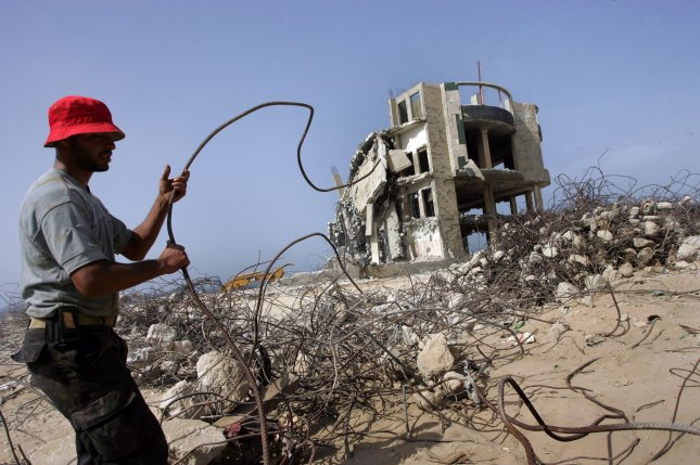 Palestinian workers collect iron from the ruins of a beach front hotel in Gaza City, on October 18, 2010 that was destroyed during Israel's 22-day military offensive in winter 2009. Israel prevents the entry of construction materials to Gaza because of blockade. Israel and Egypt have blockaded Gaza since the militant group Hamas seized power there in 2007. Gaza residents use tunnels to haul in supplies from Egypt. UPI/Ismael Mohamad