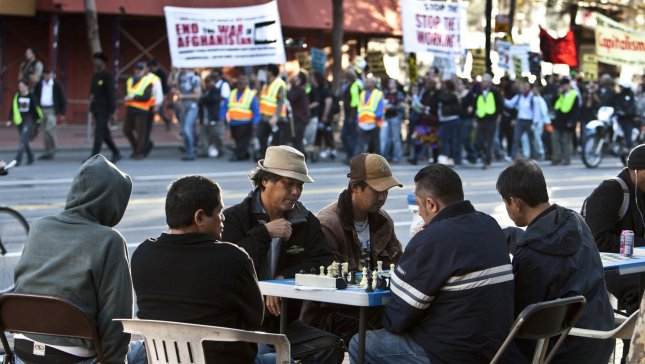 Chess players on Market Street in San Francisco take no notice of a noisy demonstration against the war in Afghanistan. (File/UPI/Terry Schmitt)